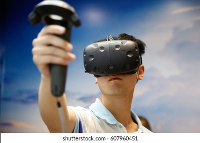 jinan, CHINA - May 28, 2016: Man tries virtual reality HTC Vive headset during and hand controls, HTC virtual reality exposition, at the jinan.