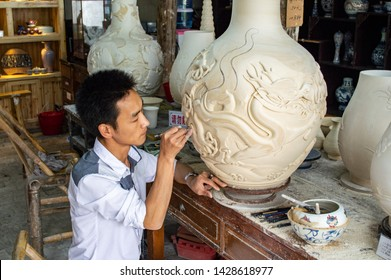 "Jingdezhen, Jiangxi province / China - May 29th 2014: Porcelain Craftsman working in the Pottery workshop. Jingdezhen is famous for its porcelain production and known as the ""Porcelain Capital"""
