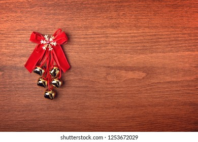 Jingle bells, bows and Christmas decorations on a light wooden background. Place for text.