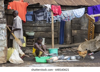 JINJA, UGANDA - MAY 16: An African kid wash the dishes in Jinja, Uganda in 2017