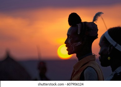 JINKA, ETHIOPIA - CIRCA 2011 - A Hamar man watches a bull jumoping ceremony as the sunsets. The bull jumping ceremony is the Hamar mens's rite of passage into adult hood.