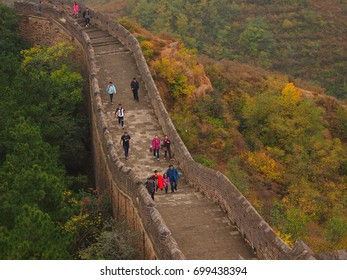 Jinshanling, China - 07 October, 2016: Tourists walk along the Great Wall of China, which has different colour trees on each side, showing the autumn colours