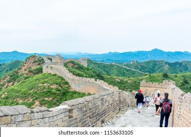 JINSHANLING, CHINA - May 24, 2016: Tourists Walking on the Inside Top of The Great Wall of China as it Bends its way through the Jinshanling Mountains