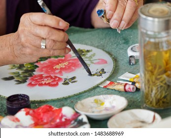 Jinxi, China - June 29, 2018: Unrecognizable artist painting Chinese traditioanl round silk fans in Jinxi town near Shanghai, focused on the butterfly.