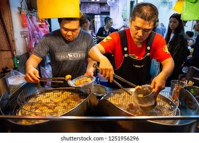 JIUFEN, TAIWAN - NOVEMBER 6: Two men cook stinky tofu at the night market of Jiufen on November 6, 2018 in Jiufen, Taiawan.