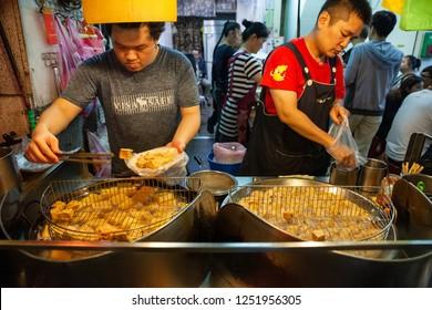 JIUFEN, TAIWAN - NOVEMBER 6: Two men cook stinky tofu at the street market of Jiufen on November 6, 2018 in Jiufen, Taiawan.