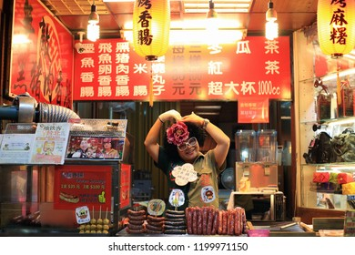Jiufen, Taiwan - October 8, 2018: A lady selling famous wild boar sausage at Jiufen old street, New Taipei,Taiwan