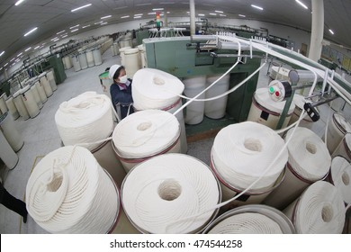 Jiujiang, China-Jan 19, 2013 In the eastern part of China, Cotton group in spinning production line factory, the workers are tight spinning. Textile is traditional pillar industries in china.