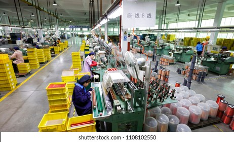 JIUJIANG CHINA-March 30, 2018: female workers operate machines in the workshop to produce motor parts, such as small motors, which are invested in sweatshops in Jiujiang, Jiangxi, Eastern China.