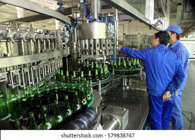 JIUJIANG CHINA-Nov22, 2013, Tsingtao Brewery Jiujiang Co., Ltd. production workshop, workers are operating assembly line production of beer. Tsingtao equipment level, technology are world-class level.