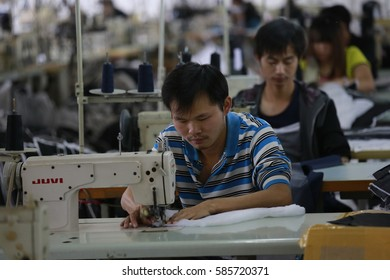 JIUJIANG CHINA-Sep26, 2013: Jiangxi, Jiujiang, male sewing workers in a garment factory production workshop processing exports to Europe and the United States and Japan and other places of clothing.