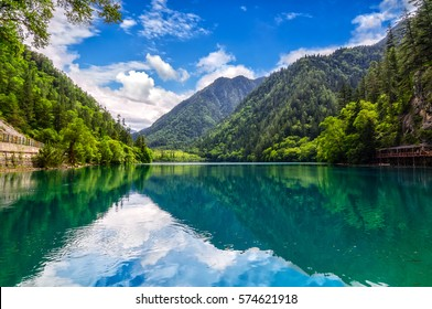 jiuzhaigou national park reserve. Calm blue water lake, blue sky, mountains and green forest.
