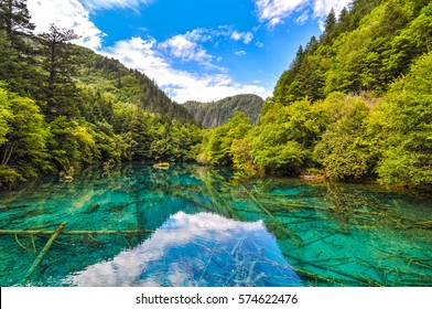 jiuzhaigou national park reserve. Green lake with crystal clear water surrounded by mountains and forests.