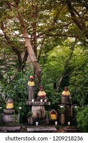 Jizo Bosatsu stone monk statues with bib and hat at Nittai-Ji in Nagoya, Japan. Jizo is a guardian of aborted children and kids who die prematurely.