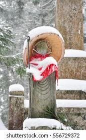 Jizo or stone statue wearing red apron under snow in Koyasan, Japan