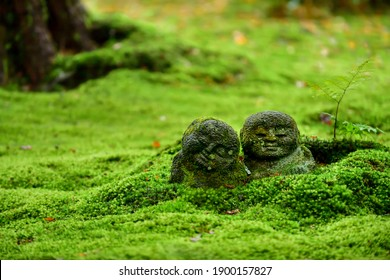 Jizo stone stature (little Japanese Buddhist monk) at the Japanese garden covered by moss with fall colors, Sanzenin temple, Kyoto, Japan