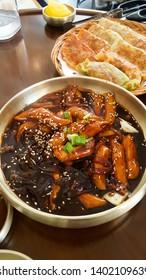 Jjajang tteokbokki, ricecakesinblack soybeansauce, serving on the brass plate