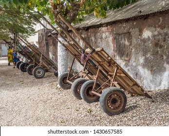 Joal-Fadiouth, Senegal. A few carts are standing next to the building on the island Joal-Fadiouth. Town and commune is in the Thiès Region at the end of the Petite Côte of Senegal. Africa.