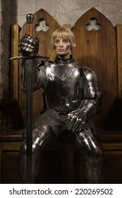 Joan of Arc. Girl in a knight's armor in the interior of a medieval castle