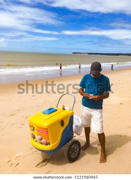 Joao Pessoa, Paraiba, Brazil - June 25, 2018 - Street vendor deals with popsicles and money on the beach