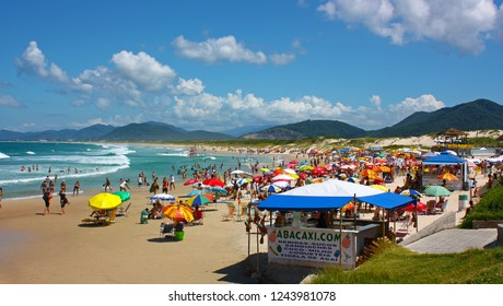 JOAQUINA BEACH, FLORIANOPOLIS, SANTA CATARINA, BRAZIL - MARCH 22, 2009: Many colorfull sunshades at the beach. People relaxing and enjoying the sun and the sea. Famous destination in latin america.