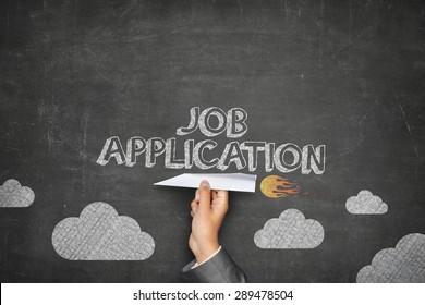 Job application concept on black blackboard with businessman hand holding paper plane
