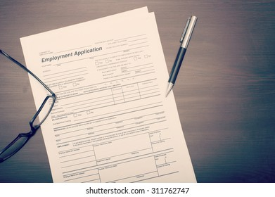 Job application form on desk with pen and glasses viewed from above