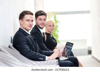 Job candidates. Three people in formalwear waiting in line while sitting at the chairs and holding laptop in their hands