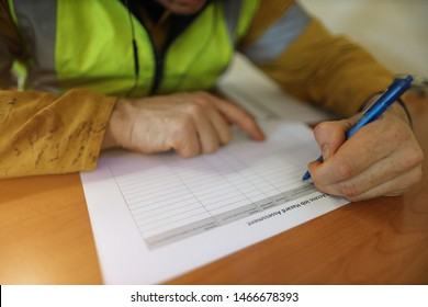 Job hazard Assessment (JHA) paper document work on the table with defocused male hand writing with blue pencil at the background construction site Perth