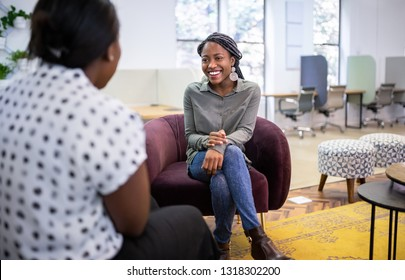 Job interview in co-working space by recruiter. Black african woman in her twenties being interviewed by a woman employer