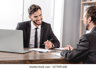 Job Interview. Employer looking at candidate cheerful checking resume sitting in office