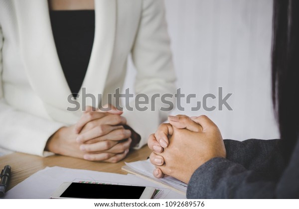 job interview and hiring concept with the female HR manager listening to the candidate presenting her resume