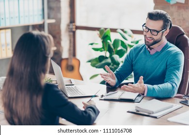 Job interview - Joyful, successful businessman asking candidate questions, sitting at desk in workplace on chair, girl making notes