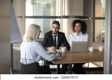 Job interview lead by arab and african HR managers in applicant is elderly woman rear view answer questions, people seated at desk indoors, job-hunting after 50 years chances opportunities concept