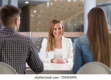 Job interview.Young happy woman being interviewed by two business people in the office