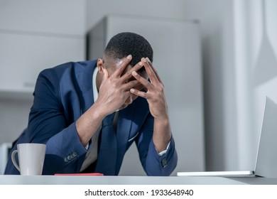 Job loss. Elegant dark-skinned man closing his head and looking frustrated