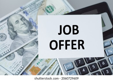 job offer inscription on paper, which lies on the calculator on the table next to the dollor, currency