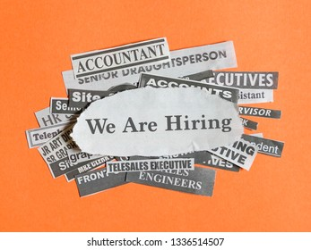 Job opportunity concept- job titles or vacancies cut from newspapers on orange with the words, We are hiring