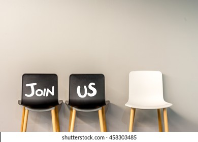 Job recruiting advertisement represented by 'JOIN US' texts on the chairs. One chair is colored differently to represent the hiring position to be recruited and filled.