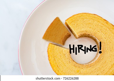 Job recruiting advertisement represented by 'HIRING!' texts on the plate surrounded by the circle Baumkuchen, roll layer cake. One slice is colored differently to represent the hiring position.