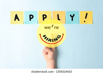 """Job recruiting advertisement represented with finger touching a button with text """"we're hiring"""" simulating a happy smiling face. The word APPLY is written on multi colored notes with a blue background"""