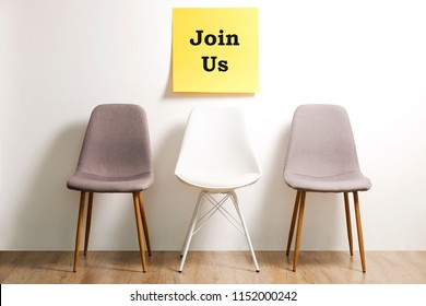 Job recruitment advertisement, JOIN US text written on yellow wall poster, three empty loft style chairs. Human resources campaign to find workers for vacant job. Close up, copy space, background.