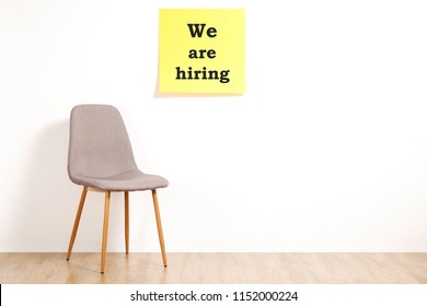 Job recruitment advertisement, WE ARE HIRING text written on yellow wall poster, empty loft style chair. Human resources campaign to find new workers for vacant job. Close up, copy space, background.
