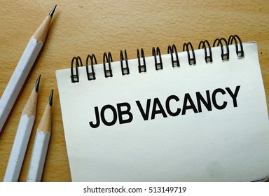 Job Vacancy text written on a notebook with pencils