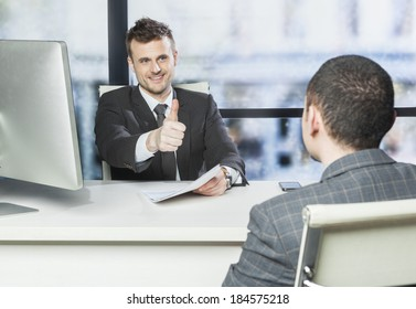 Job well done - concept , boss showing thumb up to one of his employee in the office