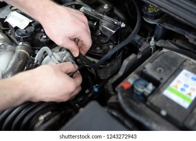 job and workplace - mechanic in a workshop repairing a car