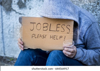 Jobless man begging on a street holding a handwritten sign for help covering his face as he sits on the sidewalk in jeans and a hoodie holding a cup for coins