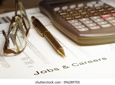 Jobs and careers with a calculator, ballpoint pen and pair of reading glasses.