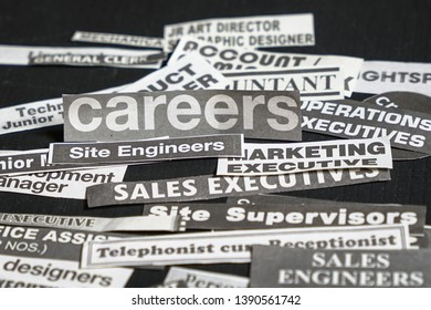 Jobs or careers concept: multiple job titles or occupations cut off from newspaper with Careers on top of the pile and on black background