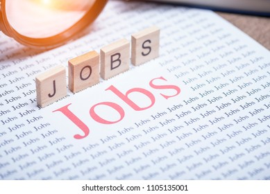 """Jobs search concept, Big red text word """"Jobs"""" on white paper and Magnifying glass for jobs search"""